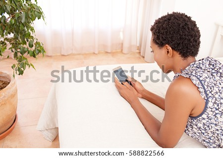 Rear side portrait of african american female laying relaxing on home bed holding smart phone with blank screen, networking in indoors bedroom. Black woman using technology lifestyle, home interior.