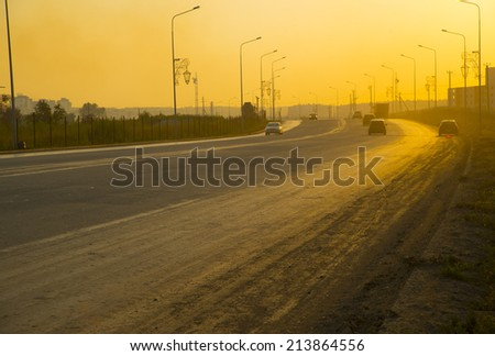 Rear-side view of a luxury car on sunset  Background of sunrise asphalt road with a lot auto and yellow sunny sky backdrop - stock photo