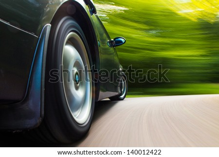 Rear side view of black car in turn with heavy blurred motion. - stock photo