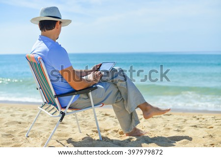 Rear side view om man using digital tablet relaxing on chair at the ocean beach. Blue sky outdoors background