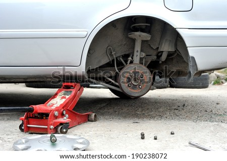 rear spindle of car in maintenance process - stock photo