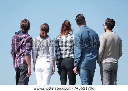 rear view.a group of young people looking at copy space
