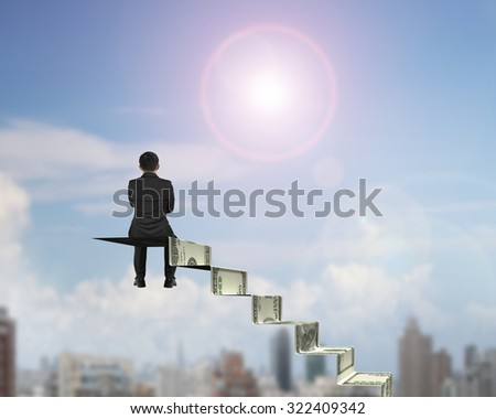 Rear view businessman sitting on top of money stairs, with sunny sky cityscape background. - stock photo