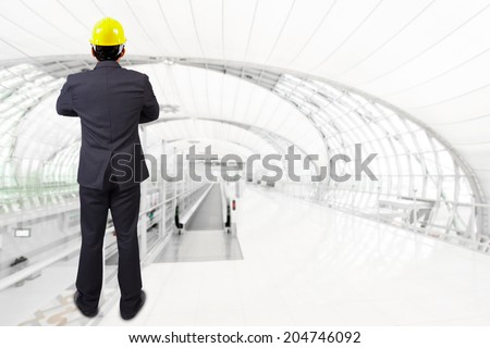 rear view businessman standing cross one's arm and yellow helmet for workers security at futuristic airport interior with concept of real estate and engineering - stock photo