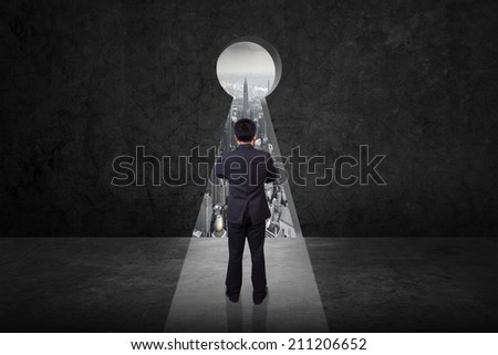rear view businessman standing cross one's arm front of keyhole on old grunge black wall against urban scene balcony over looking city dusky before rain falling  - stock photo