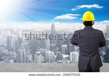 rear view engineer standing cross one's arm chest at high building construction site against blue sky with in concept ecology and real estate