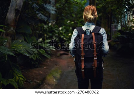 Rear view female hiker walking in the wild jungle forest, hipster girl at sport hike activity  outdoors, focus on the backpack - stock photo