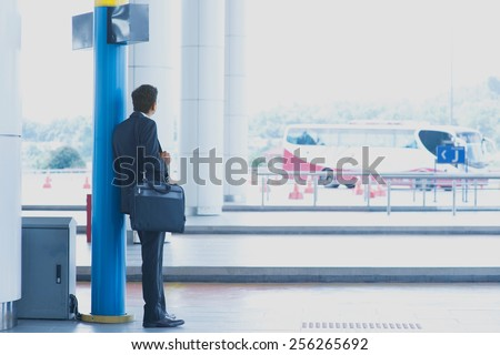 Rear view full body Asian Indian business man waiting bus at public bus station. - stock photo
