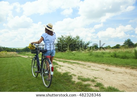 Rear view full length portrait of young woman wearing straw hat and a casual clothing while pushing her bike in a field.