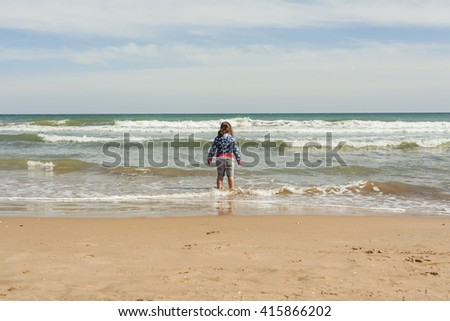 Rear view full shot girl walking to the shore of the beach in a sunny day in spring. - stock photo