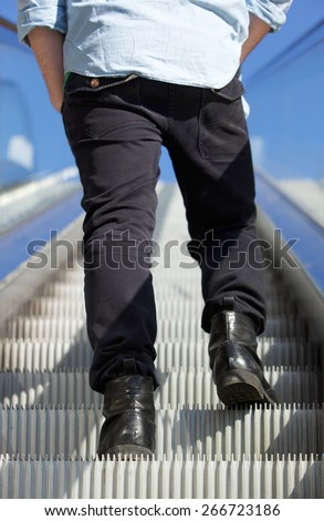 Rear view low angle man standing on escalator - stock photo