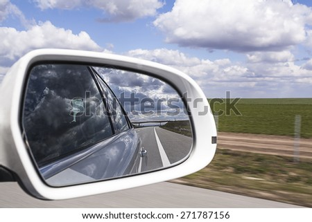 Rear view mirror reflecting freeway with cloud - stock photo