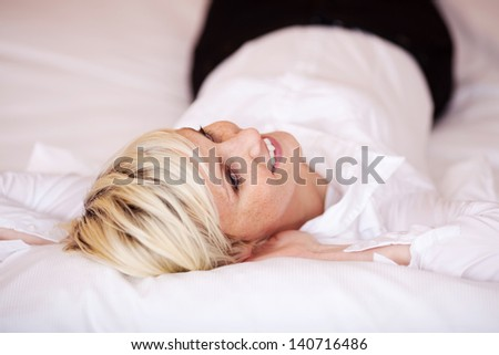 Rear view of a beautiful young blonde woman relaxing in bed with a lovely big smile - stock photo