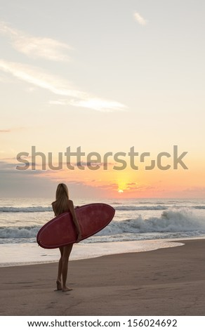 Rear view of a beautiful young woman surfer girl in bikini with red surfboard at a beach sunset or sunrise - stock photo