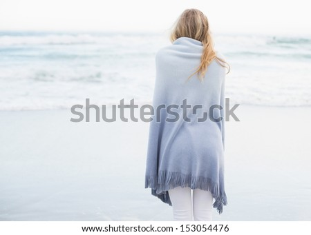 Rear view of a blonde woman warming up in a blanket on the beach - stock photo