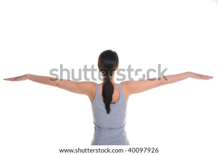 Rear view of a brunette woman doing yoga with her arms outstretched, isolated on a white background. - stock photo
