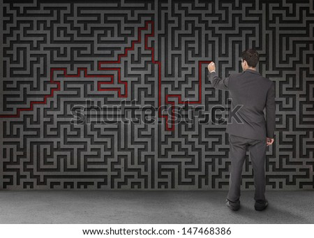 Rear view of a businessman drawing a red line through black maze on wall - stock photo
