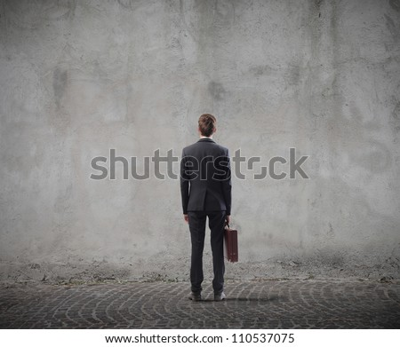 Rear view of a businessman standing in front of a wall