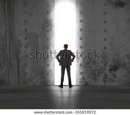 Rear view of a businessman standing in front of the exit light - stock photo