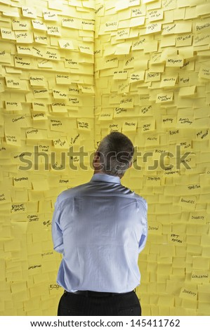 Rear view of a businessman standing in front of wall covered in sticky notes - stock photo