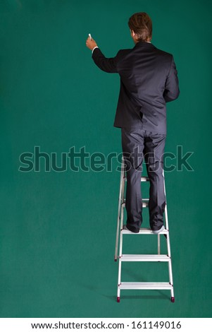 Rear View Of A Businessman Standing On Ladder Writing On Chalkboard - stock photo