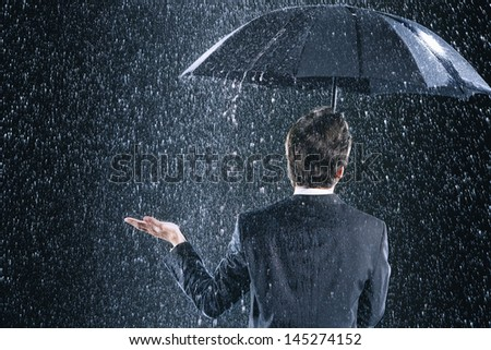 Rear view of a businessman staying dry under umbrella during downpour - stock photo