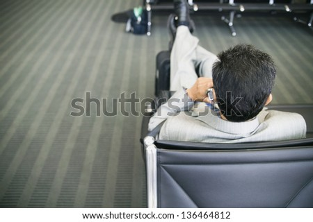 Rear view of a businessman talking on a mobile phone in an airport lounge - stock photo