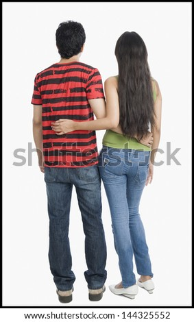 Rear view of a couple standing with arm around