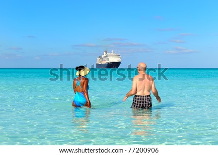 Rear view of a couple walking on the beach and watching cruise ship - stock photo