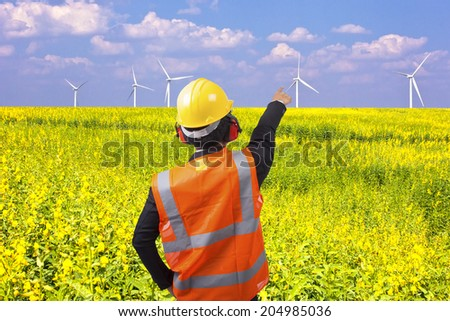 rear view of a engineer in suit pointing at wind turbines in a flower field eco power concept - stock photo
