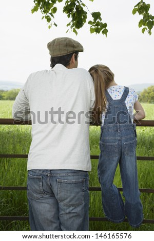 Rear view of a father with daughter looking at lush landscape by fence