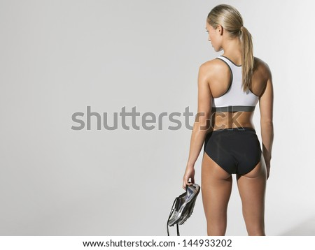 Rear view of a female athlete holding shoes against white background - stock photo