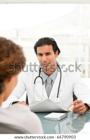 Rear view of a female patient during an appointment with her doctor at the hospital - stock photo