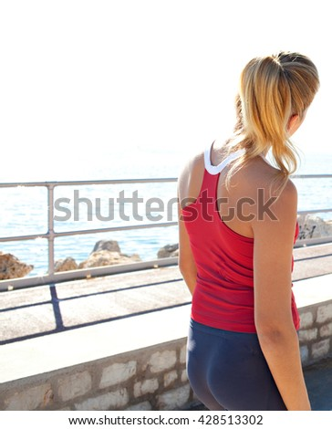 Rear view of a fit and sporty teenager girl taking a break from exercising, contemplating the sea on a sunny summer day by the beach coast, sea outdoors. Adolescent fitness lifestyle, healthy living. - stock photo