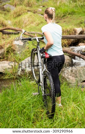 Rear view of a fit woman rolling her bike about to cross a river