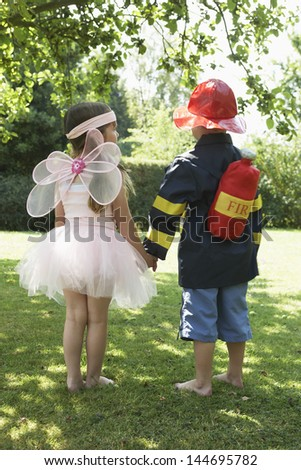 Rear view of a girl and boy dressed as fairy and fireman in park  - stock photo