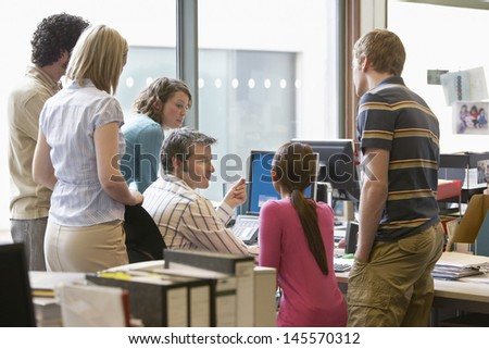 Rear view of a group of multiethnic office workers around colleague using computer