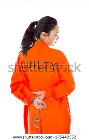 Rear view of a handcuffed Asian young woman in prisoners uniform - stock photo