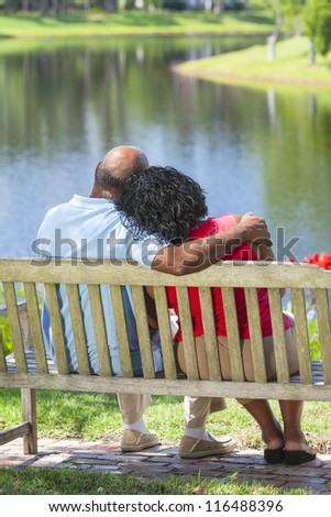 Rear view of a happy romantic senior African American couple sitting on a park bench embracing looking at a lake or river - stock photo