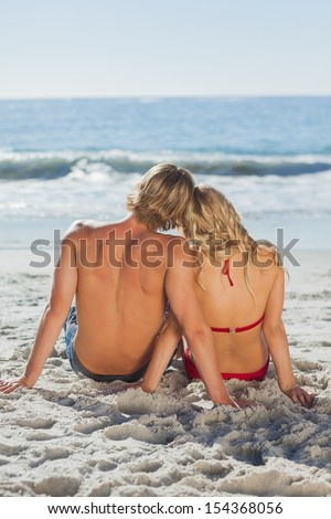 Rear view of a happy tanned couple sitting in front of the sea on holidays