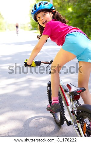 Rear view of a little girl on bike looking at camera