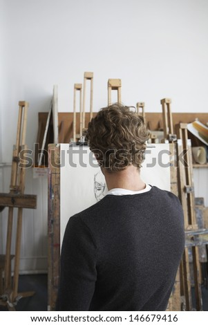 Rear view of a male artist drawing charcoal portrait in studio - stock photo
