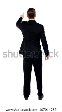 Rear view of a male model pointing at copy space over white background