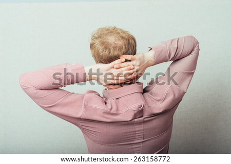 Rear view of a male office worker relaxing at desk - stock photo
