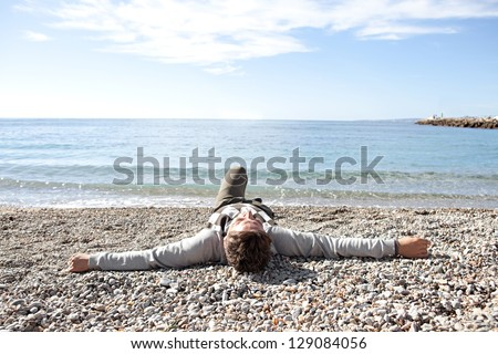 Rear view of a man laying down on the shore a white pebbles beach during a sunny day in winter with a blue sky. - stock photo