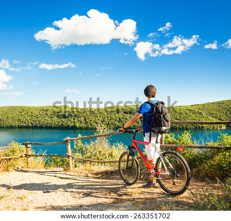 Rear View of a Man with a Bicycle on Beautiful Nature Background. Healthy Lifestyle and Travel Concept. Copy Space. - stock photo