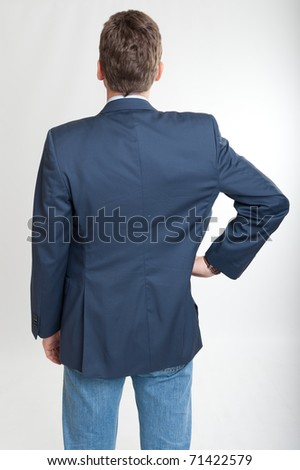 Rear view of a man with a hand on his hip - stock photo