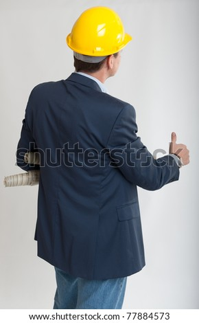 Rear view of a man with a safety helmet consulting blueprints with his thumb up - stock photo