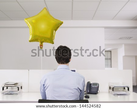 Rear view of a man working alone beside balloon in office - stock photo