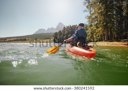 Rear view of a mature man canoeing in a lake. Senior man paddling kayak on a summer day.